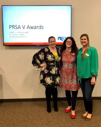 3 females stand together in front of PRSA V Awards sign
